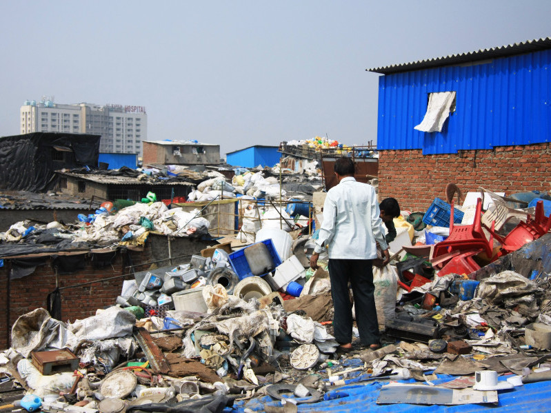 Workers sorting through piles of consumer plastic waste in the Dharavi slum rooftops, Mumbai, India