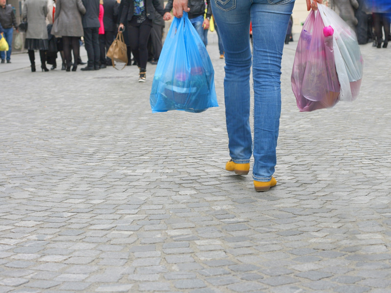 A woman with single use plastic shopping bags