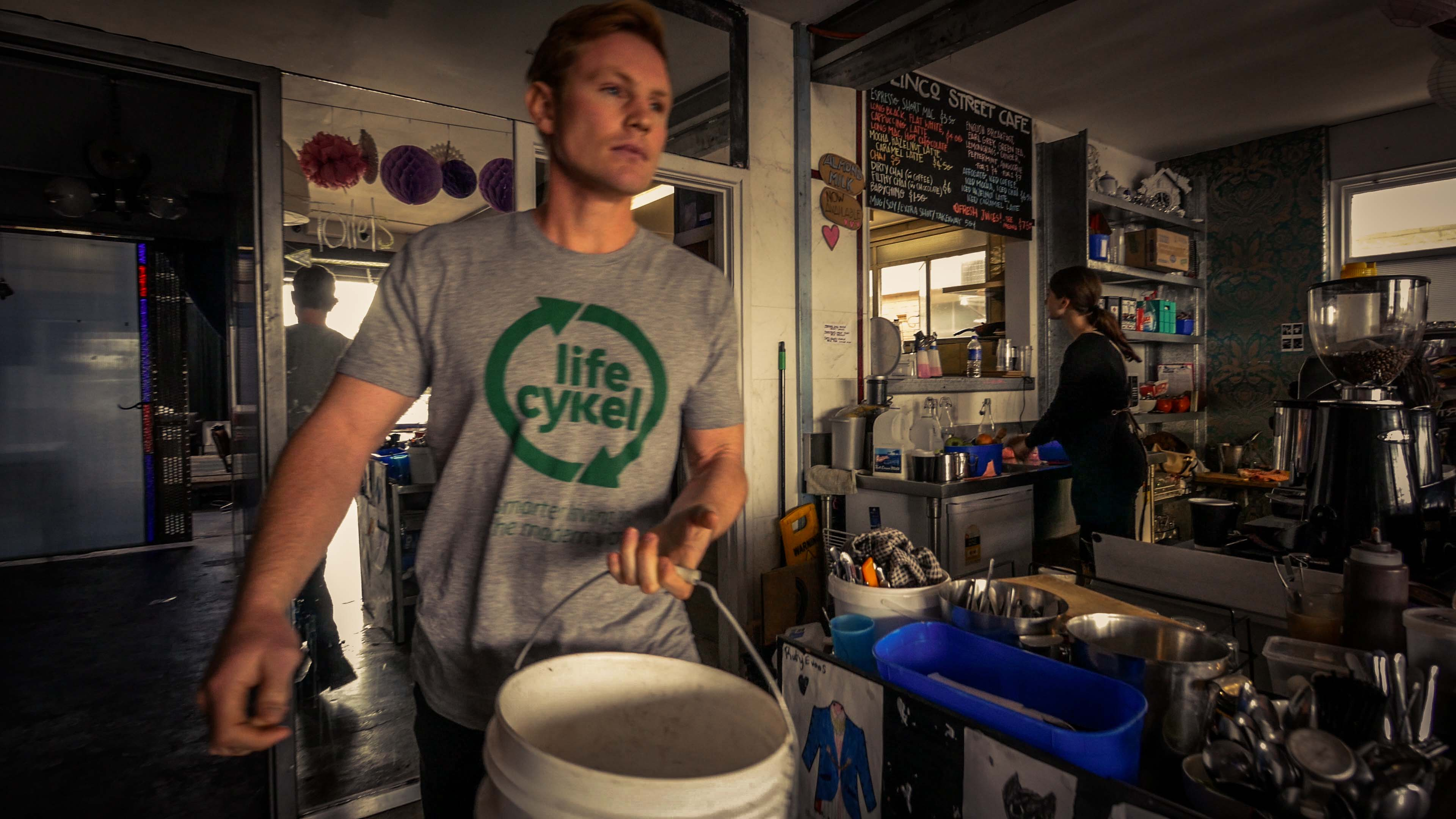 Julian Mitchell of Life Cykel collects waste coffee grounds from a Fremantle cafe