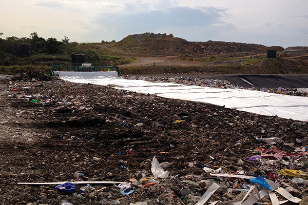 Tarp Deployment System to reduce landfill costs